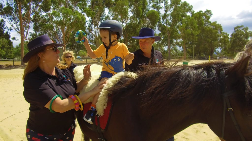 Jaxon riding with assistance from HorsePower volunteers